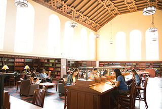 Students studying in a large study space, multiple bookcases filled with books line the walls while a vaulted ceiling and several tall arched windows create a bright and airy space