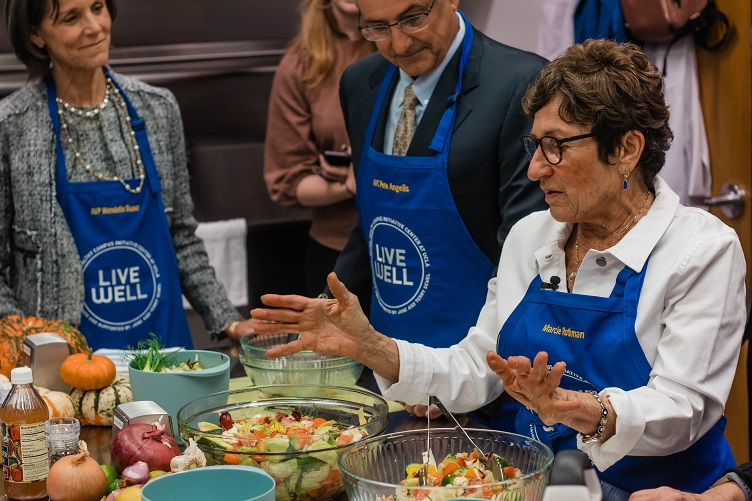 Two women and one man, wearing blue aprons with the Live Well logo, stand in front of a table of fresh produce and ingredients