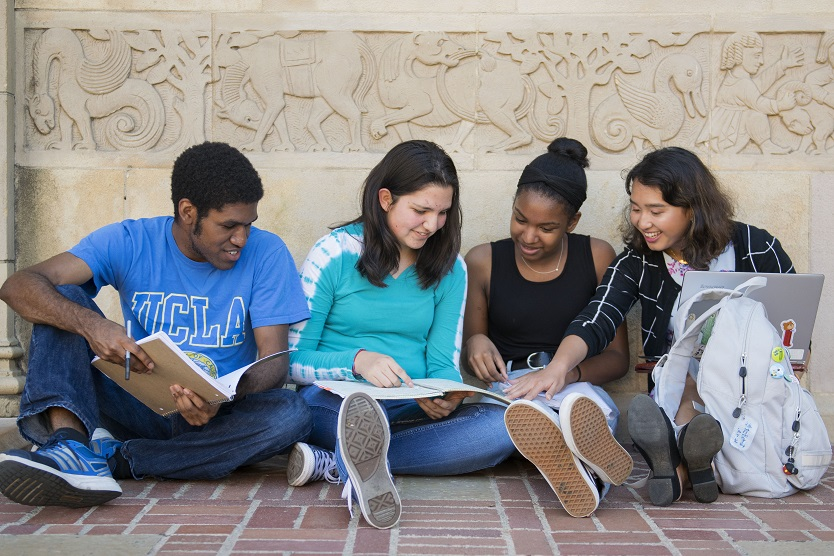 Four students of various ethnicities sit on a brick sidewalk beneath a frieze. They are exhanging ideas while holding notebooks and a laptop.