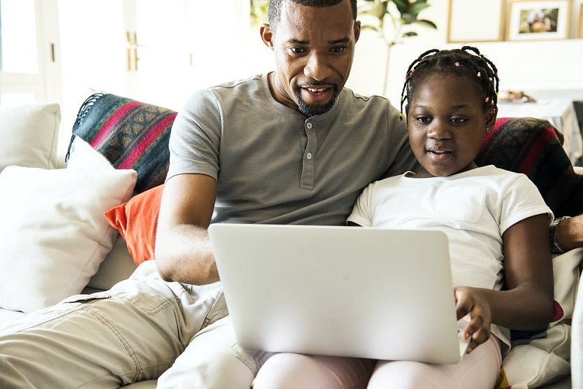 An African American father and daughter sit side-by side on a sofa and look at a laptop the girl is holding.