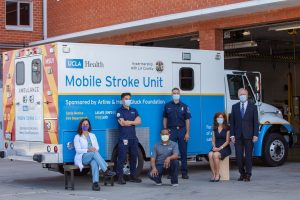Four medical professionals and a formally dressed couple all wear masks while posing in front of UCLA's Mobile Stroke Unit at a fire station.