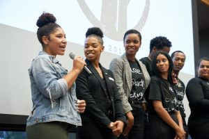 A young Black woman speaks into a microphone on stage as three of her classmates look on with smiles.