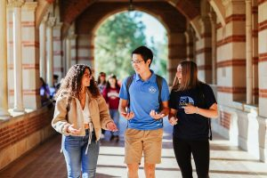 Two female and one male student converse while walking under the brick archway of Royce Hall on the UCLA campus