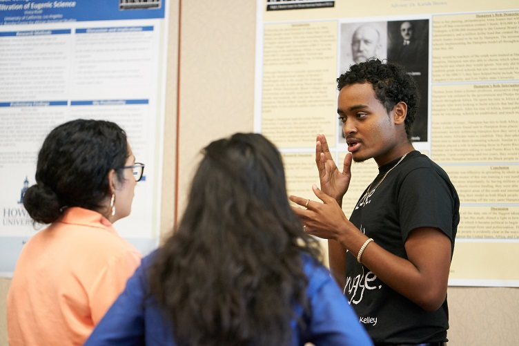 Man wearing black t-shirt with white lettering gestures while speaking to two women; a poster is displayed in the background
