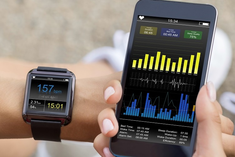 Smartwatch on a person's left wrist and smartphone in their right hand; both devices display data