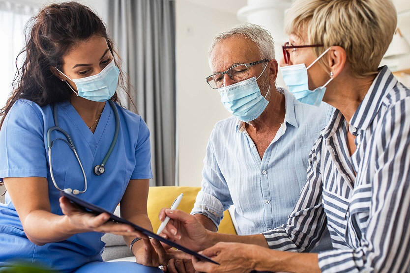 Younger medical professional in scrubs and mask shows clipboard to masked older couple