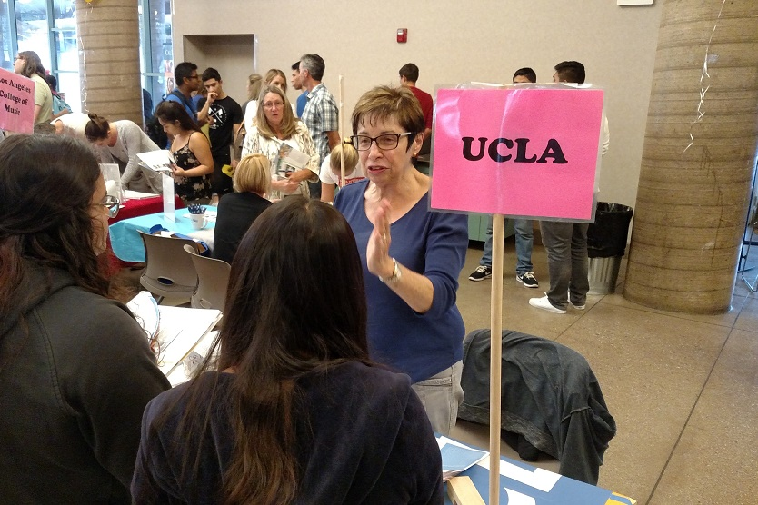 Person with short brown hair and glasses speaks to students from behind a table with a UCLA sign