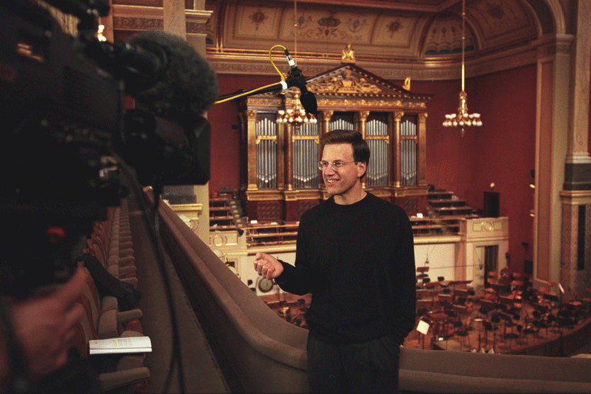 Donor Lowell Milken being interviewed in an ornate concert hall