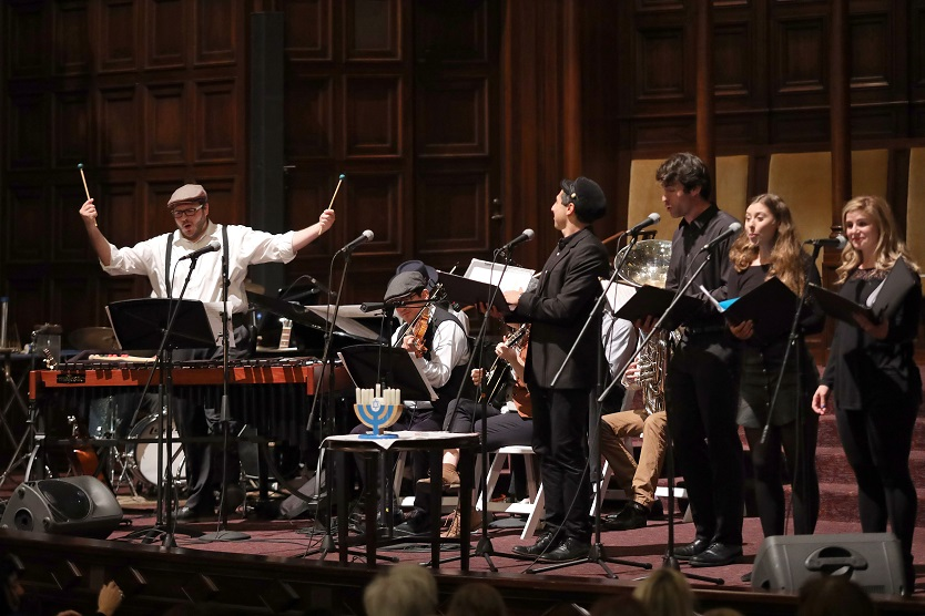 Performers on a stage include a percussionist, four vocalists, and various instrumentalists, with a small menorah at the front.