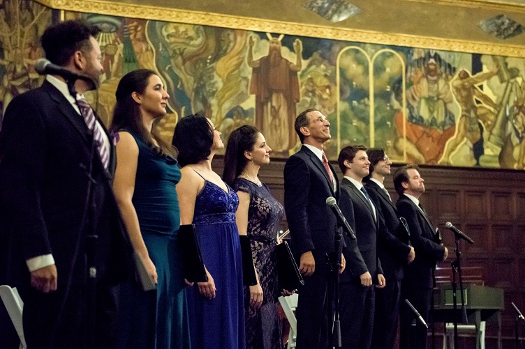 Eight vocalists in formal dress stand smiling on stage in front of a religious mural.