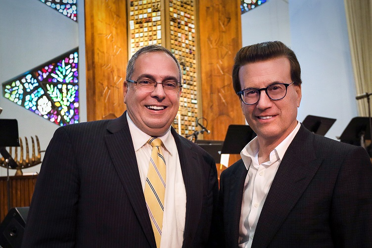 Two white men in glasses, one wearing a dark suit and striped yellow tie and the other wearing a dark blazer with no tie, smile at the camera.