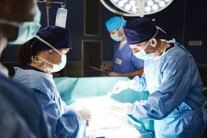 Team of busy surgeons in scrubs and masks work over an operating table